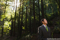 A middle aged businessman is standing deep in the forest or woods and looking up towards the tops of the trees. The man is wearing a business suit with a green necktie. Sunlight has a hard time penetrating to the forest floor.